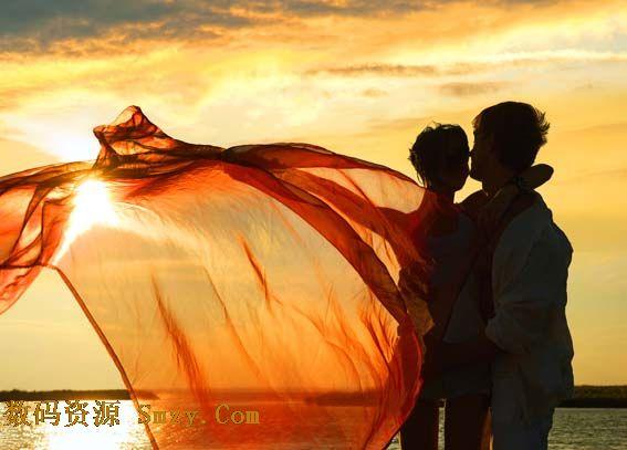 夕阳海边轻纱飞舞下情侣拥抱高清图片