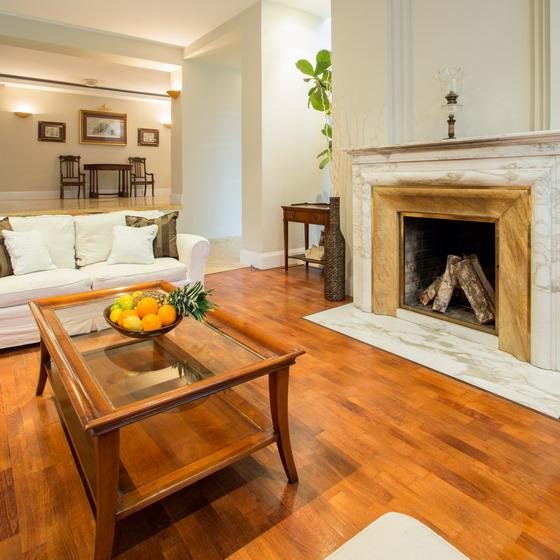 这所房子的装修风格是欧式的,房间里有壁炉,摆放着沙发,茶几等家具