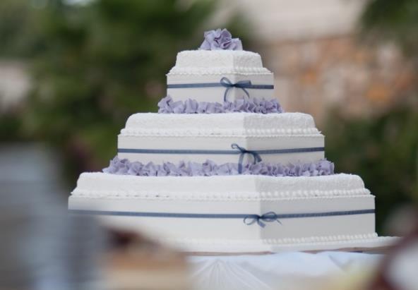 你们需要婚礼蛋糕的设计图吗?婚礼蛋糕高清素材图片中是三层的婚礼蛋糕,婚礼蛋糕和一般的蛋糕是不一样的,精致的设计使得蛋糕看起来非常的漂亮,简约中带有浪漫的气息,蛋糕上面是白色的奶油和紫色的奶油形成的,紫色的奶油是提供美感的,这么漂亮的蛋糕看定会受到很多人欢迎的哦!